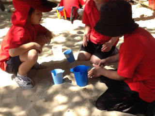 Year 1 doing maths in the sandpit with various containers used for measuring